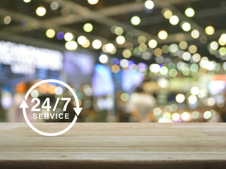 24/7 service icon on wooden table over blur light and shadow of shopping mall, Full time service concept Stock Photo