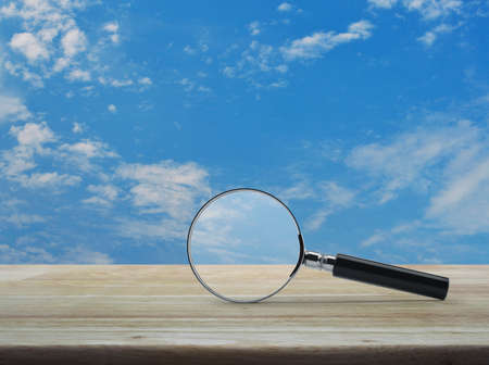 Magnifying glass on wooden table over blue sky with white clouds, Business analyzing concept