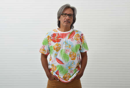 Serious elderly traveler asian man wearing summer shirt and glasses keeping hands in pockets, looking at the camera over white wall, Business summer holiday concept