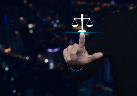 Businessman pressing law flat icon over blur colorful night light city tower and skyscraper, Business legal service concept Stock Photo