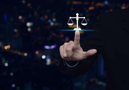 Homme d'affaires en appuyant sur l'icône plate de la loi sur la tour de la ville de lumière de nuit colorée flou et gratte-ciel, concept de service juridique d'entreprise Banque d'images