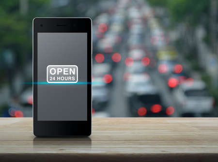 Open 24 hours flat icon on modern smart mobile phone screen on wooden table over blur of rush hour with cars and road in city, Business full time service online concept