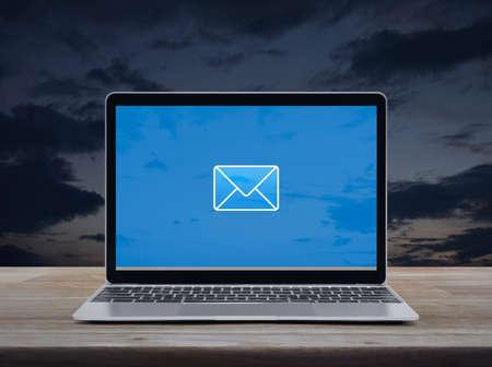 icona piatta e-mail sullo schermo del computer portatile moderno su un tavolo di legno sopra il cielo al tramonto, Business contattaci online concept
