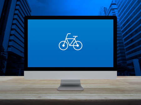 Bicycle flat icon with modern laptop computer on wooden table over office city tower and skyscraper, Business bicycle shop online concept