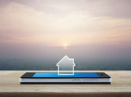 House icon with copy space on modern smart mobile phone screen on wooden table over office city tower and skyscraper at sunset, vintage style, Businesss real estate online concept