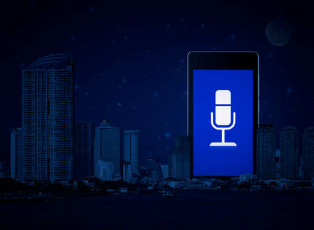 Microphone flat icon on modern smart mobile phone screen over office city tower, river and fantasy night sky, Business communication online concept