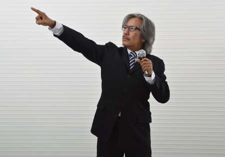Confident elderly asian businessman in black suit and eyeglasses speaking with microphone and pointing finger up for the future over white wall, Business presentation and seminar concept Reklamní fotografie