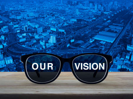 Black glasses with our vision text on wooden table over modern city tower, street, expressway and skyscraper