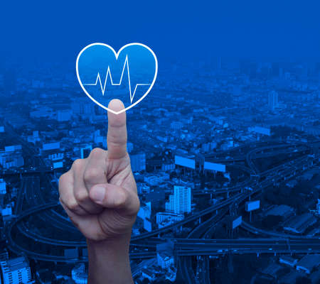 Heart beat pulse flat icon over modern city tower, street, expressway and skyscraper, Business medical health care service concept Reklamní fotografie