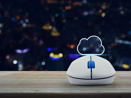Cloud icon with copy space and wireless computer mouse on wooden table over blur colorful night light city tower and skyscraper, Cloud computing concept