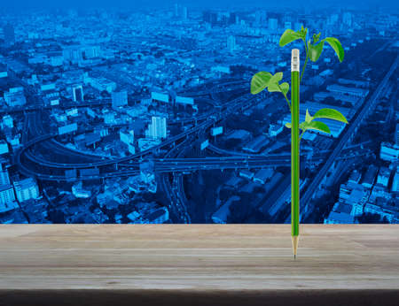 Eco green pencil with leaf on wooden table over modern office city tower and skyscraper, Business ecology concept