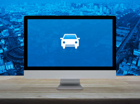 Taxi car flat icon on desktop modern computer monitor screen on wooden table over city tower, street, expressway and skyscraper, Business transportation service online concept