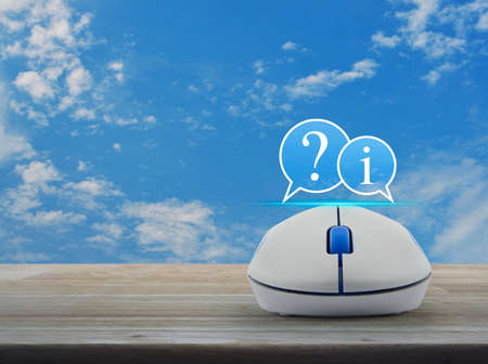 Question mark and information chat icon with wireless computer mouse on wooden table over blue sky with white clouds, Business customer support online concept Stock Photo