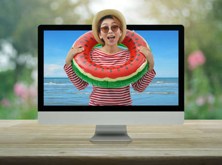 Happy young asian woman wearing red stripped shirt, sunglasses, straw hat and jeans in watermelon inflatable ring with tropical sea and desktop modern computer monitor screen on wooden table over blur pink flower and tree, Business summer holiday online concept