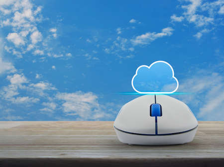Cloud icon with copy space and wireless computer mouse on wooden table over blue sky with white clouds, Cloud computing concept