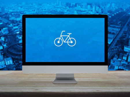 Bicycle flat icon with modern laptop computer on wooden table over city tower, street, expressway and skyscraper, Business bicycle shop online concept Reklamní fotografie