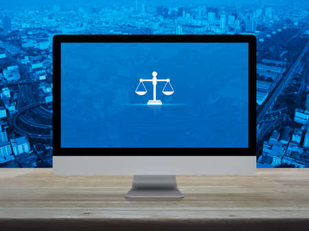 Law flat icon on desktop modern computer monitor screen on wooden table over city tower, street, expressway and skyscraper, Business legal service online concept