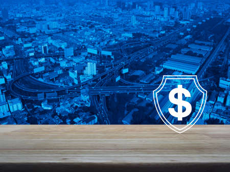 Dollar with shield flat icon on wooden table over modern city tower, street, expressway and skyscraper, Business money insurance and protection concept