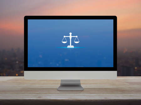 Law flat icon on desktop modern computer monitor screen on wooden table over blur of cityscape on warm light sundown, Business legal service online concept Фото со стока