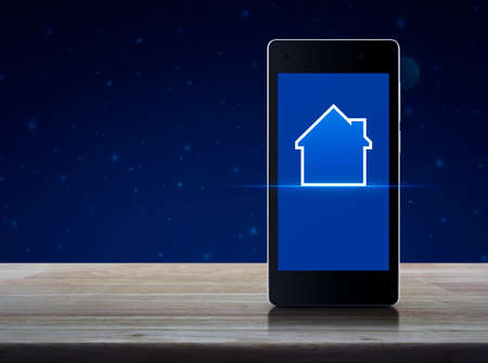 House icon with copy space on modern smart mobile phone screen on wooden table over fantasy night sky and moon, Businesss real estate concept