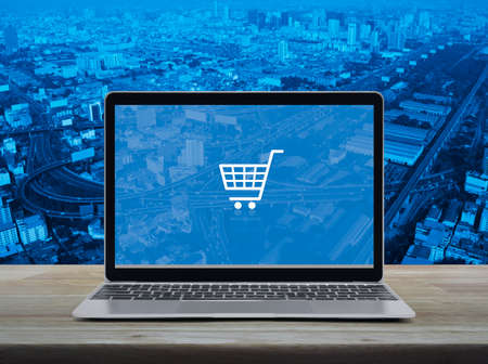 Shopping cart flat icon with modern laptop computer on wooden table over city tower, street, expressway and skyscraper, Business shop online concept Reklamní fotografie