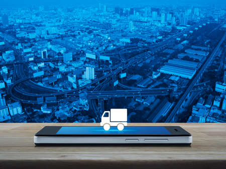Truck delivery flat icon on modern smart mobile phone screen on wooden table over city tower, street, expressway and skyscraper, Business transportation online concept