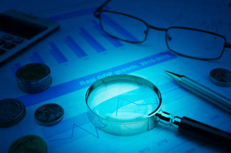 Magnifying glass, pen, coins, calculator and glasses on growth financial graph, Business success concept Stock fotó