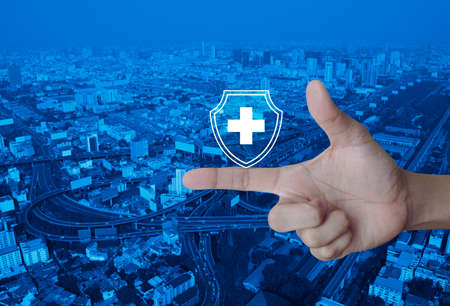 Cross shape with shield flat icon on finger over modern city tower, street, expressway and skyscraper, Business healthy and medical care insurance concept