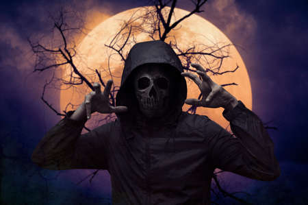 Human skull in jacket standing over dead tree, full moon and spooky cloudy sky, Halloween mystery concept