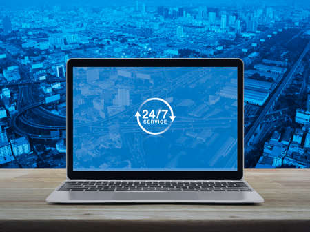 24 hours service icon with modern laptop computer on wooden table over city tower, street, expressway and skyscraper, Business full time service online concept Stock Photo