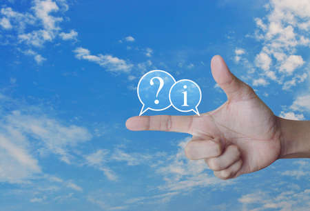 Question mark and information chat icon on finger over blue sky with white clouds, Business customer support concept
