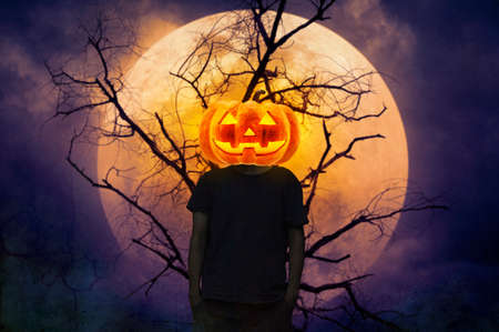 Pumpkin monster head on man body standing over dead tree, full moon and spooky cloudy sky, Halloween mystery concept