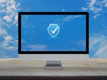 Security shield with check mark icon on desktop modern computer monitor screen on wooden table over blue sky with white clouds, Technology internet cyber security and anti virus online concept