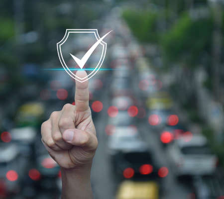Hand pressing security shield with check mark icon over blur of rush hour with cars and road in city, Internet cyber security and anti virus concept