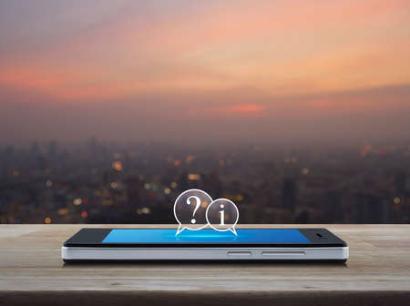Question mark and information chat icon on modern smart mobile phone screen on wooden table over blur of cityscape on warm light sundown, Business customer service and support online concept