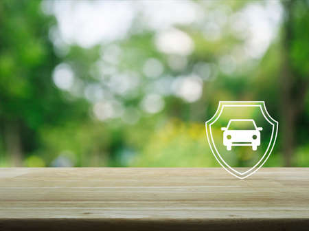 Car with shield flat icon on wooden table over blur green tree in park, Business automobile insurance concept