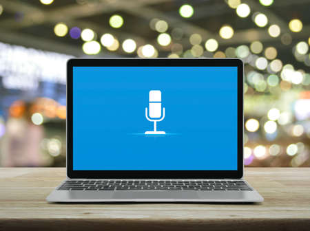Microphone flat icon with modern laptop computer on wooden table over blur light and shadow of shopping mall, Business communication online concept Stockfoto
