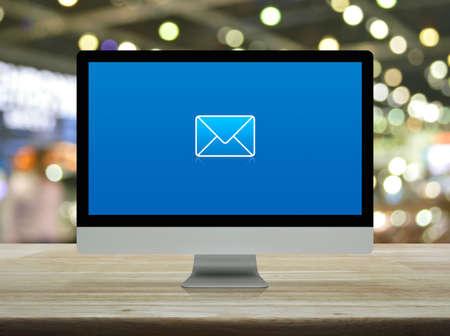 icône plate de courrier électronique sur l'écran du moniteur d'ordinateur moderne de bureau sur une table en bois sur la lumière floue et l'ombre du centre commercial Banque d'images