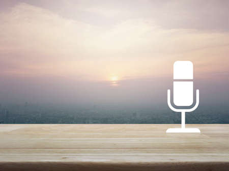 Microphone flat icon on wooden table over aerial view of cityscape at sunset, vintage style, Business communication concept
