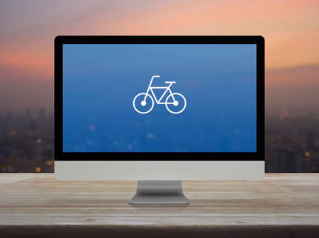 Bicycle flat icon with modern laptop computer on wooden table over blur of cityscape on warm light sundown, Business bicycle shop online concept Reklamní fotografie - 129047503