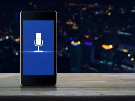 Microphone flat icon on modern smart mobile phone screen on wooden table over blur colorful night light city tower and skyscraper, Business communication online concept