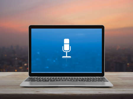 Microphone flat icon with modern laptop computer on wooden table over blur of cityscape on warm light sundown, Business communication online concept Stockfoto