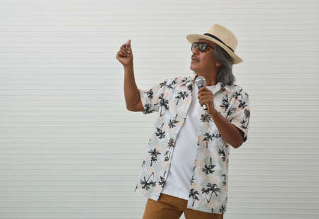 Happy senior traveler asian man wearing straw hat, sunglasses and summer shirt singing with microphone over white wall background, Summer holiday concept
