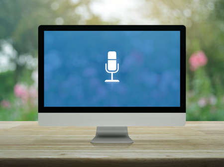 Microphone flat icon on desktop modern computer monitor screen on wooden table over blur pink flower and tree in garden, Business communication online concept