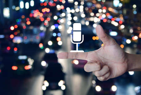 Microphone flat icon on finger over blur colorful night light traffic jam road with cars in city, Business communication concept