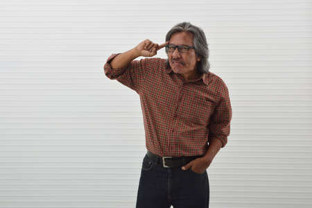 Thoughtful senior asian man in red casual shirt, blue jeans and eyeglasses pointing finger to his head over white wall background, Funny face expression pose Stockfoto - 129049580