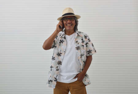 Smiling senior traveler asian man wearing straw hat, sunglasses and summer shirt talking on modern smart mobile phone over white wall background, Business summer holiday concept Stockfoto