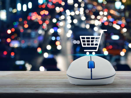 Shopping basket flat icon with wireless computer mouse on wooden table over blur colorful night light traffic jam road with cars in city, Business shop online concept Stockfoto - 129049583