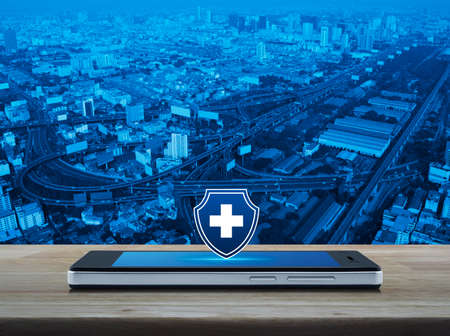 Cross shape with shield flat icon on modern smart mobile phone screen on wooden table over city tower, street, expressway and skyscraper, Business healthy and medical care insurance online concept