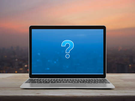 Question mark sign icon with modern laptop computer on wooden table over blur of cityscape on warm light sundown, Business customer service and support online concept